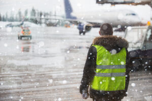 Airport manager standing under snowfall